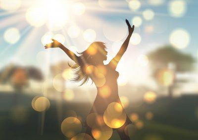 Silhouette of a happy young woman against a sunlit defocussed landscape