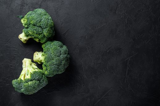 Raw green broccoli on a black background. Top view. Space for text.