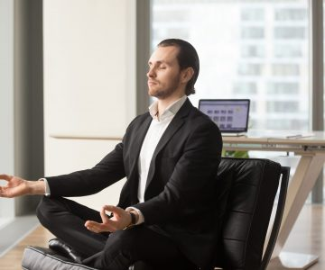 Calm young businessman meditating in yoga lotus pose in modern office. CEO taking care of his health. Reducing discomfort at workplace, staying in focus, relieving stress at work concept. Side view.