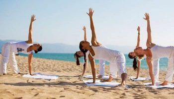 grupo-de-mujeres-practicando-yoga-en-la-playa