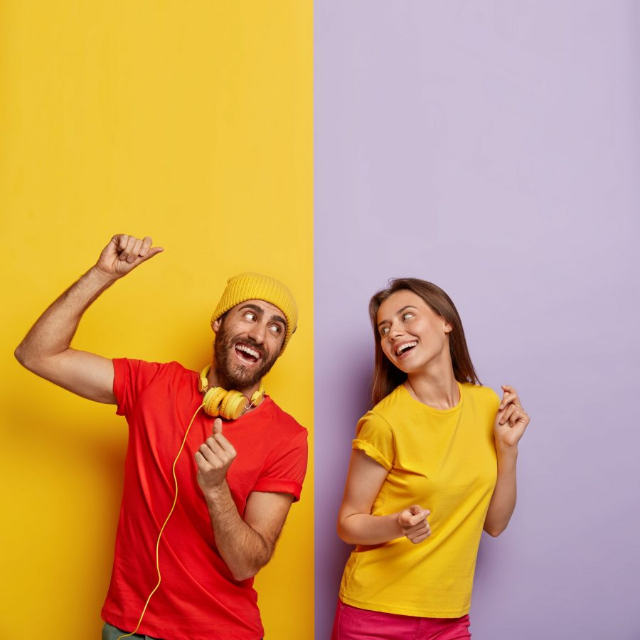 Positive couple listen music together, dance and move actively, being in good mood. Cheerful man in red t shirt, headphones on neck, spends free time with girlfriend. People and entertainment concept