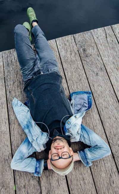 Stylish adult man lying on old wooden pier beyond lake. Dreaming happy bearded hipster in glasses portrait from above. Relaxing outdoor. Leisure lifestyle. No problem. Reflected sky in water